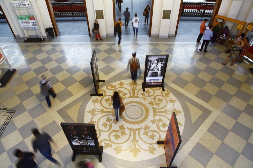 Imagem feita a partir do mezanino da Estação da Luz, mostrando o piso decorado. Pessoas circulam pelo espaço, com piso xadrez (branco e cinza claro) e uma grande rosácea amarela no centro. Há alguns paineis com fotografias espalhados pelo espaço.